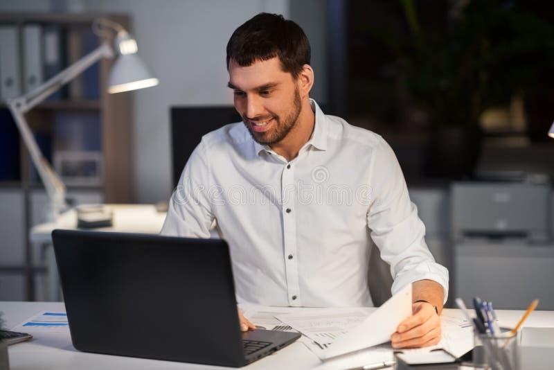 Uomo d'affari con funzionamento del computer portatile all'ufficio di notte immagine stock libera da diritti