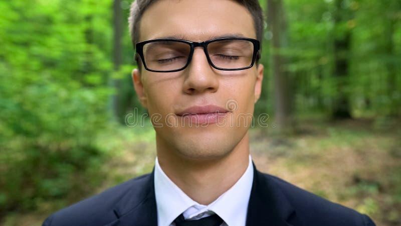 Uomo d'affari con gli occhi chiusi in foresta, sognante per lavorare in natura, fine su fotografia stock