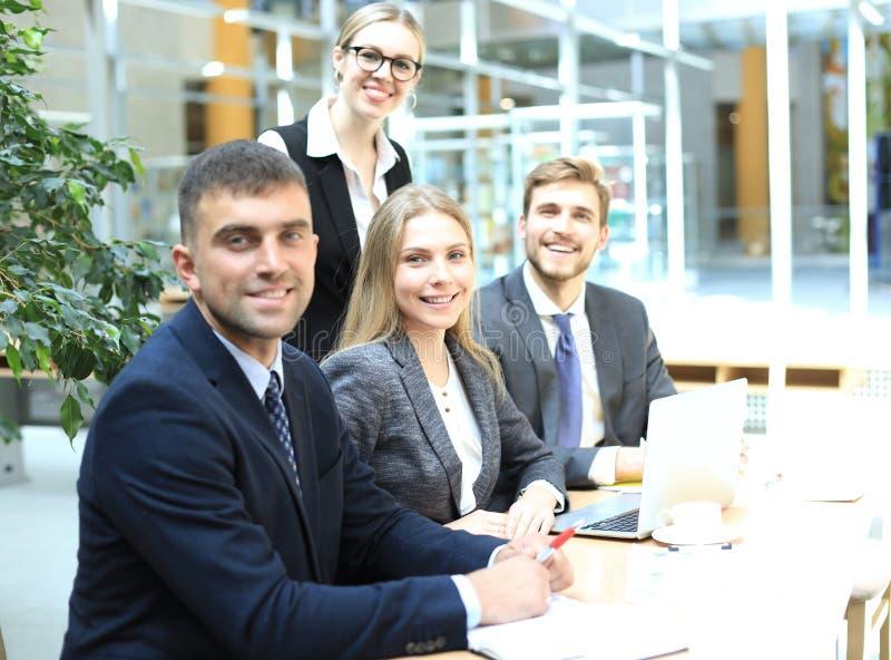 Uomo d'affari con i colleghi nei precedenti in ufficio immagine stock libera da diritti