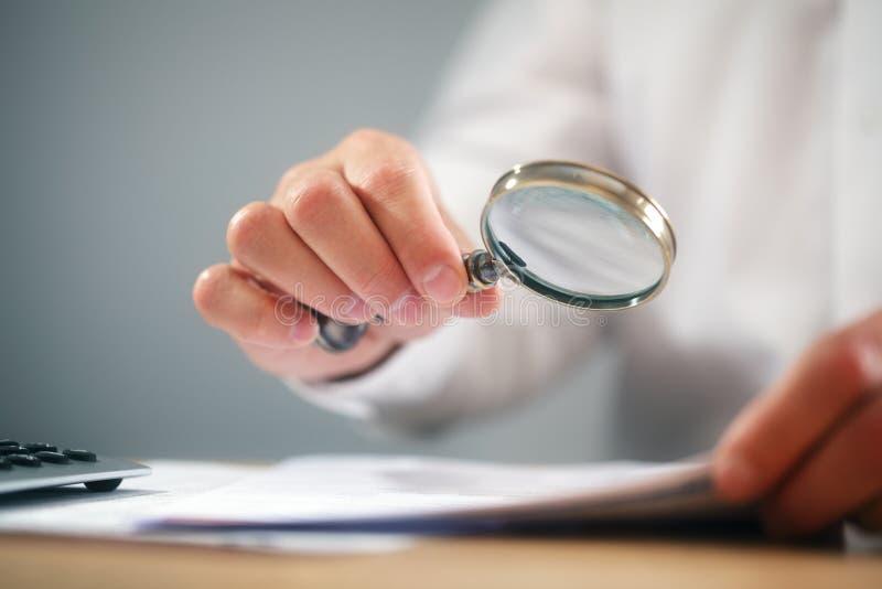 Uomo d'affari con i documenti della lettura della lente d'ingrandimento immagini stock