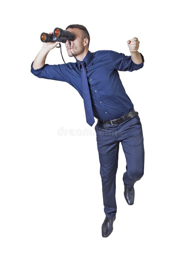 Uomo d'affari con il binocolo su una scala fotografia stock