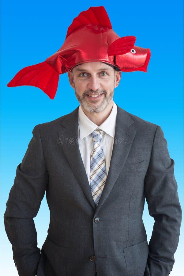 Uomo d'affari con il cappello rosso divertente nella forma di pesce fotografie stock