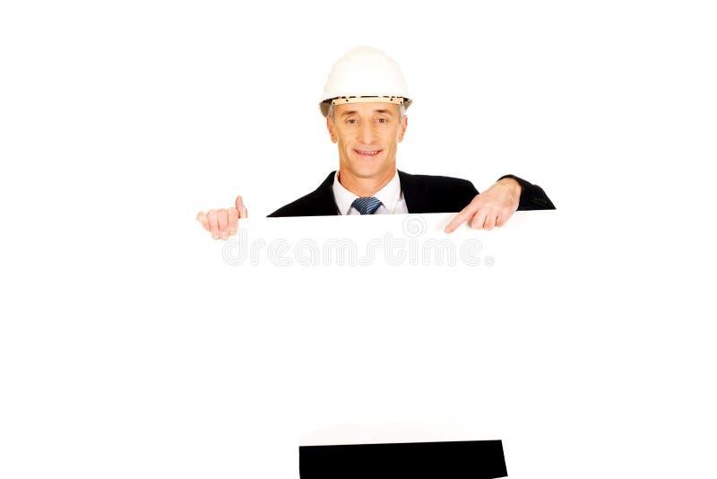 Uomo d'affari con il casco che tiene insegna vuota fotografia stock libera da diritti