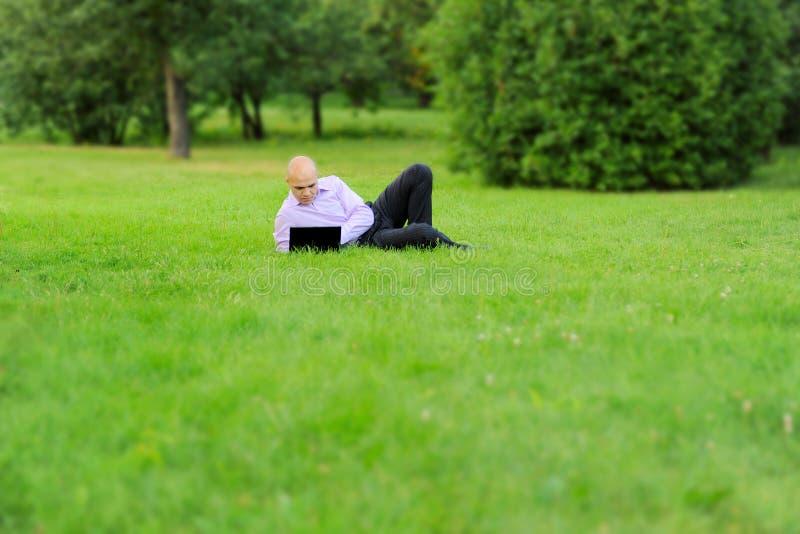 Uomo d'affari con il computer portatile che si trova sull'erba verde immagine stock libera da diritti