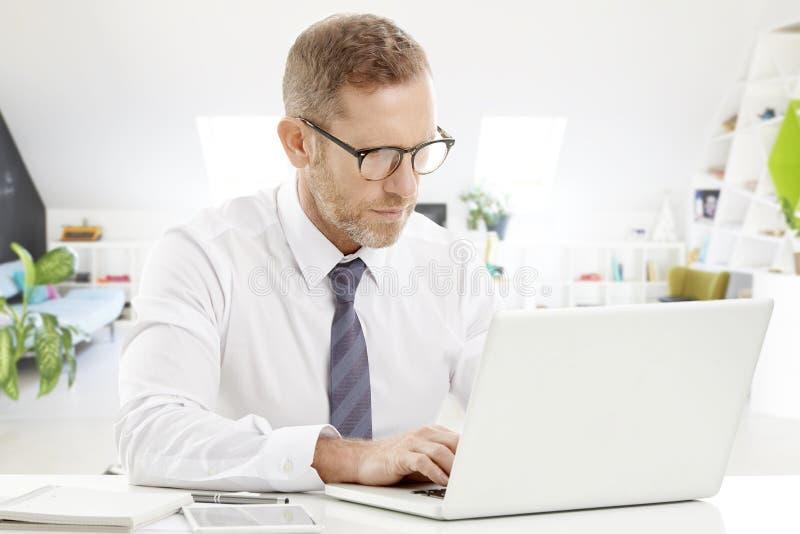 Uomo d'affari con il computer portatile ed il telefono immagini stock libere da diritti