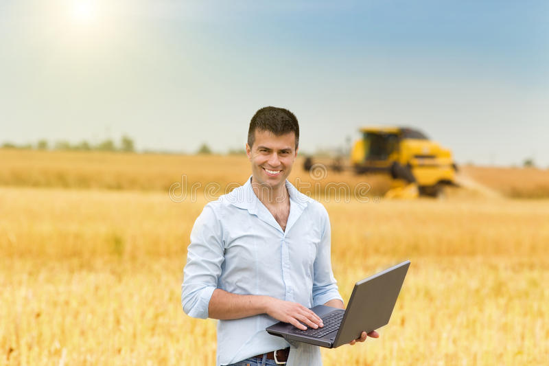 Uomo d'affari con il computer portatile nel campo immagine stock libera da diritti