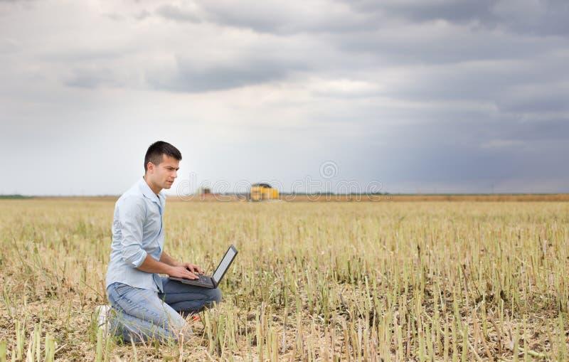 Uomo d'affari con il computer portatile nel campo fotografia stock