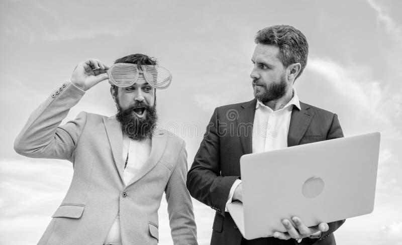 Uomo d'affari con il computer portatile serio mentre i vetri ridicoli del socio commerciale sembra divertenti Come imprenditorial fotografia stock