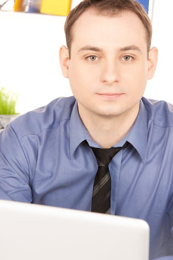 Uomo d'affari con il computer portatile in ufficio fotografia stock libera da diritti