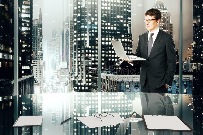 Uomo d'affari con il computer portatile in ufficio moderno con ci di megapolis di notte fotografia stock
