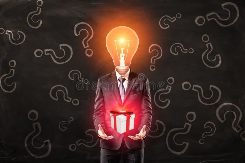 Uomo d'affari con il contenitore di regalo della tenuta della testa della lampadina con il nastro rosso in mani sul fondo nero de illustrazione di stock