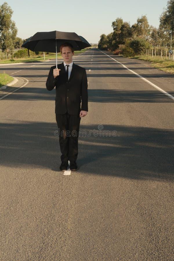 Uomo d'affari con il fronte dell'ombrello immagine stock