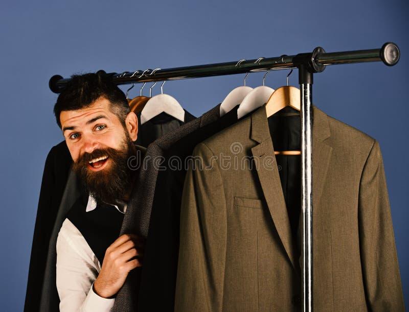 Uomo d'affari con il fronte felice vicino ai rivestimenti su fondo blu fotografie stock