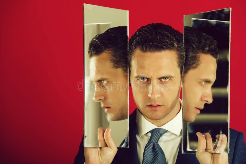 Uomo d'affari con il fronte serio che tiene due specchi in mani immagine stock libera da diritti