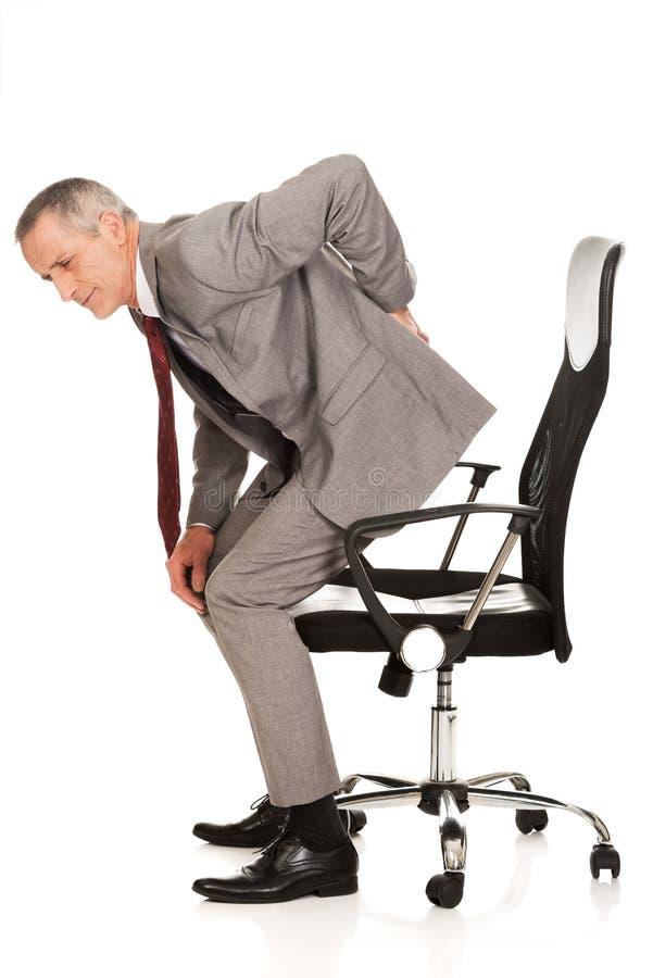 Uomo d'affari con il mal di schiena che sta su da una sedia immagini stock