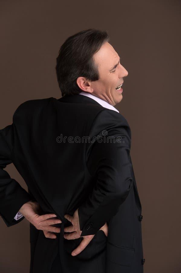 Uomo d'affari con il mal di schiena. Uomo d'affari maturo che soffre dal BAC immagine stock