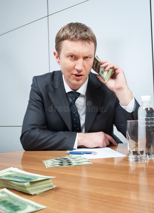 Uomo d'affari con il pacchetto dei dollari fotografia stock