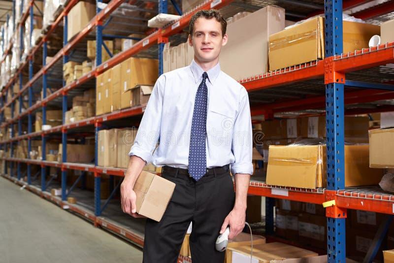 Uomo d'affari con il pacchetto e lo scanner in magazzino fotografie stock