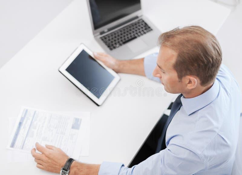 Uomo d'affari con il pc e le carte della compressa in ufficio fotografia stock libera da diritti