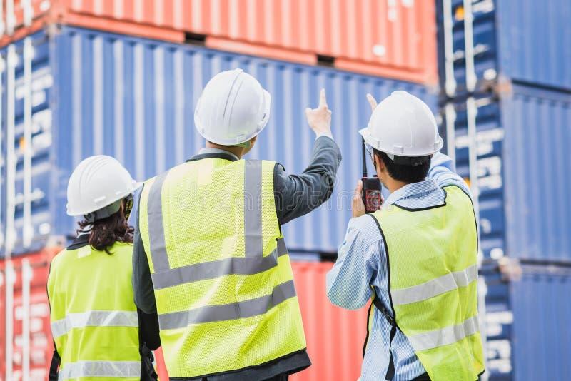 Uomo d'affari con il personale in logistico, esportazione, industria dell'importazione controllante il contenitore di carico di t fotografia stock libera da diritti
