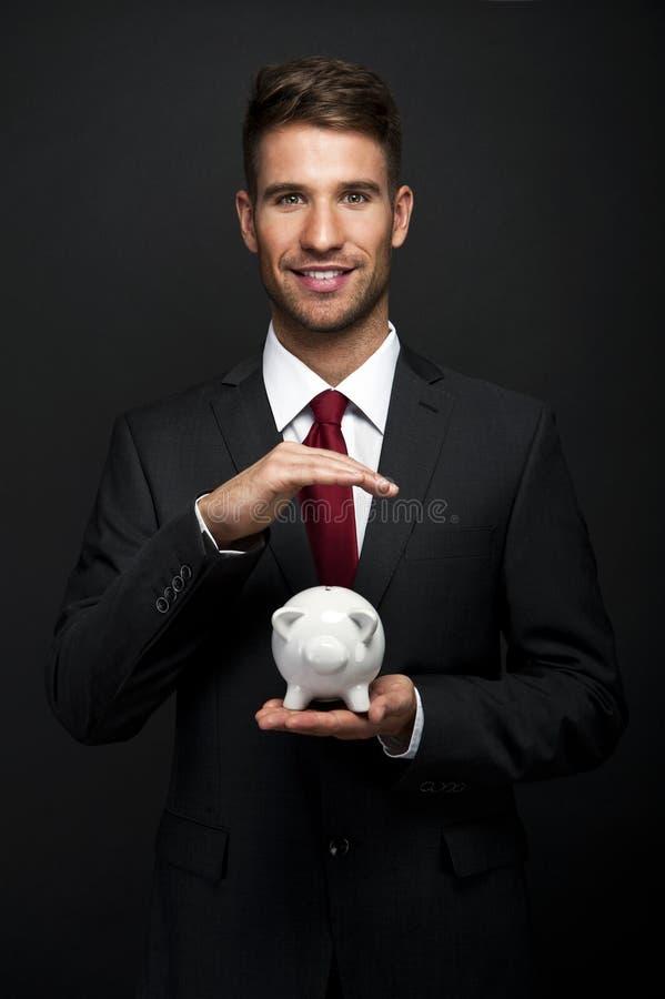 Uomo d'affari con il porcellino salvadanaio immagini stock
