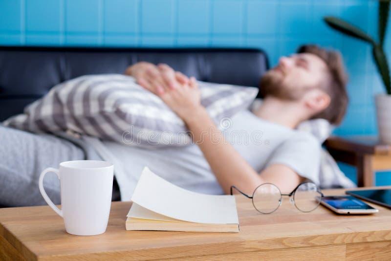 uomo d'affari con il sonno sul sofà con il libro sulla tavola a casa fotografia stock
