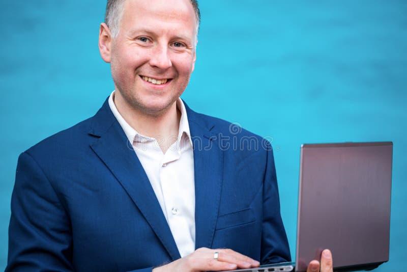 Uomo d'affari con il suo computer portatile immagine stock