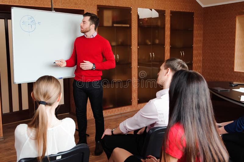 Uomo d'affari con il suo personale, gruppo della gente nel fondo all'ufficio luminoso moderno all'interno immagini stock libere da diritti