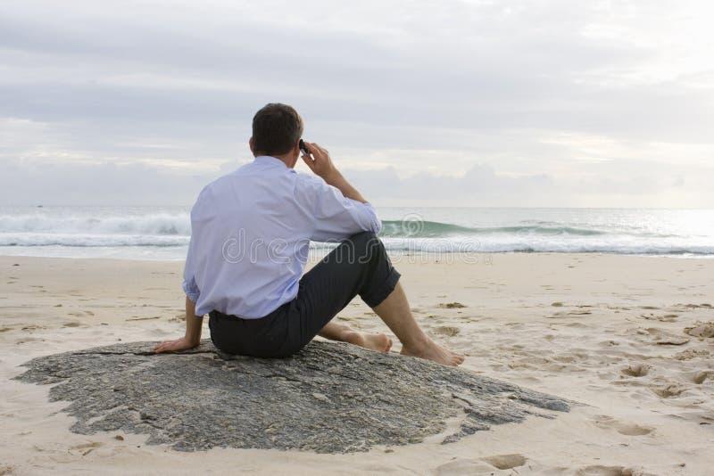 Uomo d'affari con il telefono delle cellule sulla spiaggia immagine stock libera da diritti