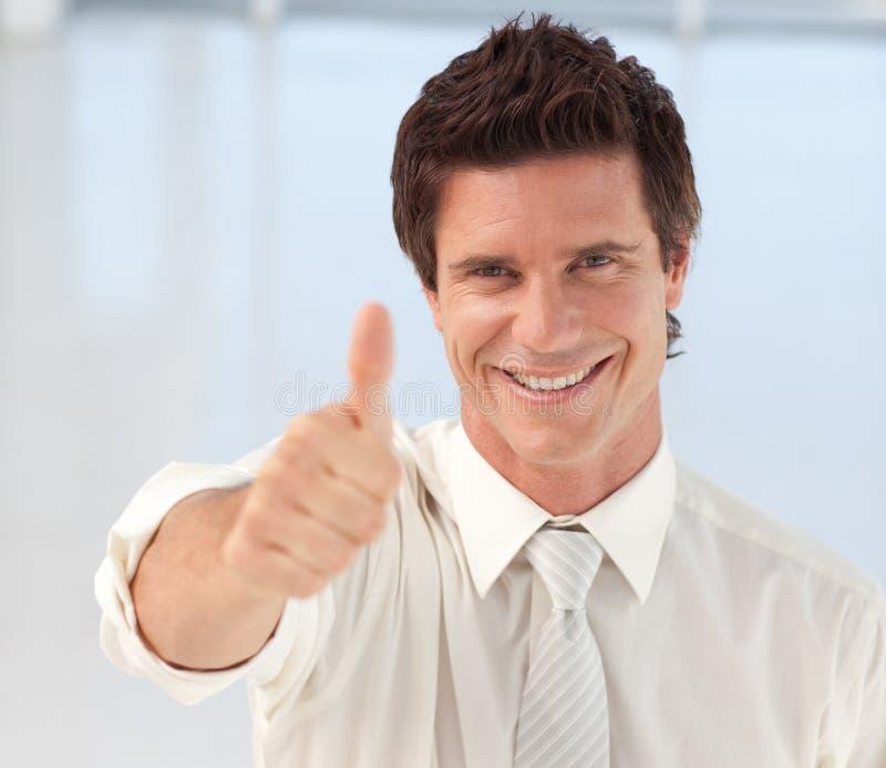 Uomo d'affari con il Thumb-up alla macchina fotografica fotografia stock libera da diritti