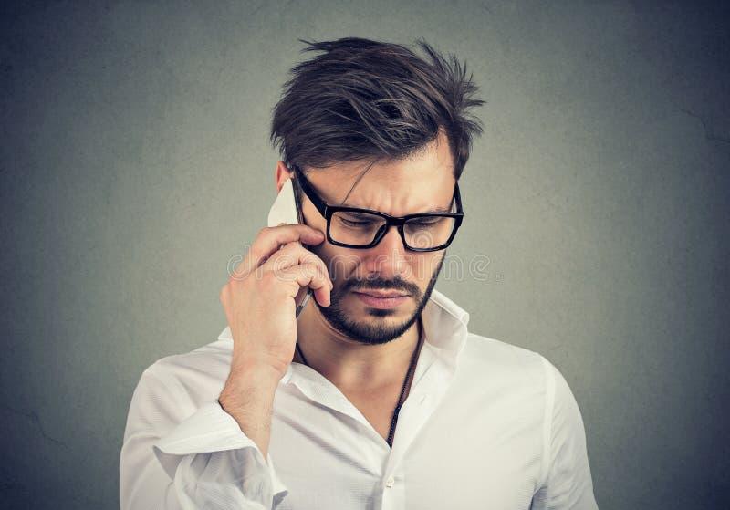 Uomo d'affari con l'espressione triste che parla sul telefono cellulare che guarda giù fotografie stock
