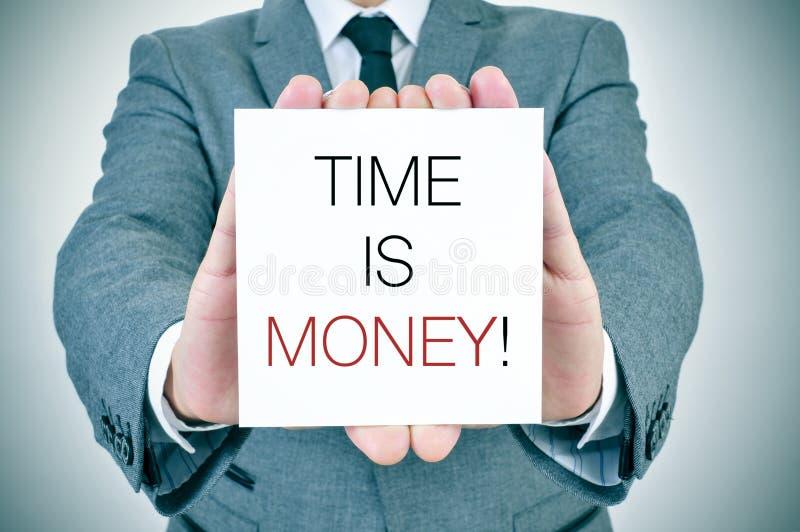 Uomo d'affari con l'insegna con testo Il tempo è denaro fotografie stock libere da diritti