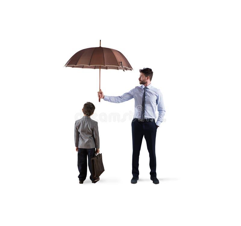 Uomo d'affari con l'ombrello che protegge un bambino Concetto di giovane protezione di partenza e di economia fotografie stock libere da diritti