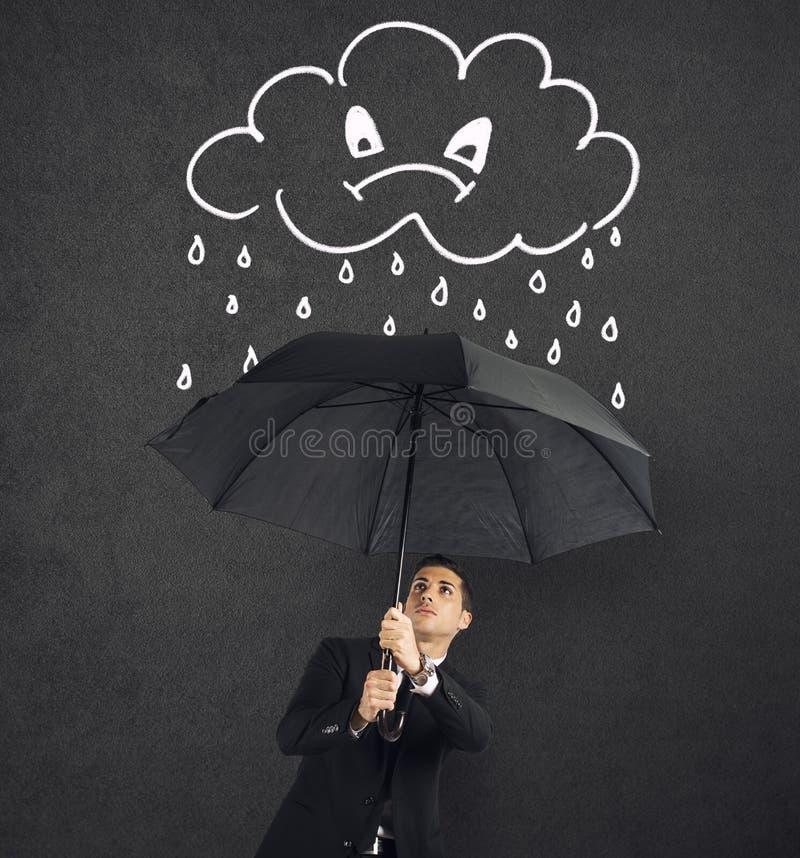 Uomo d'affari con l'ombrello e una nuvola arrabbiata con pioggia Concetto della crisi e della difficoltà finanziaria fotografie stock