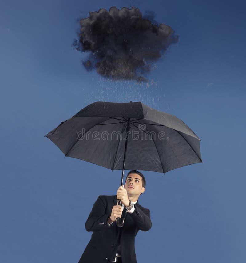 Uomo d'affari con l'ombrello e una nuvola nera con pioggia Concetto della crisi e della difficoltà finanziaria fotografia stock