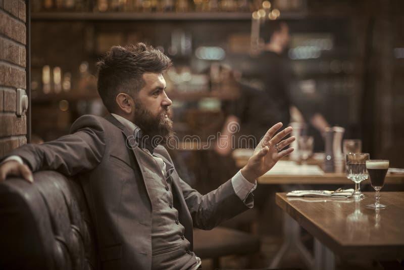Uomo d'affari con la barba lunga nel club del sigaro Il cliente sicuro della barra parla in caffè Data o riunione d'affari dei pa fotografie stock libere da diritti