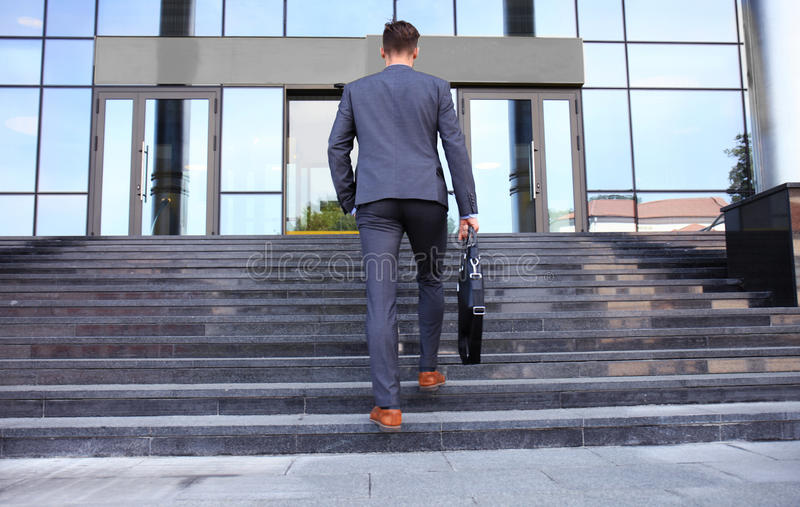 Uomo d'affari con la cartella che va sulle scale fotografie stock