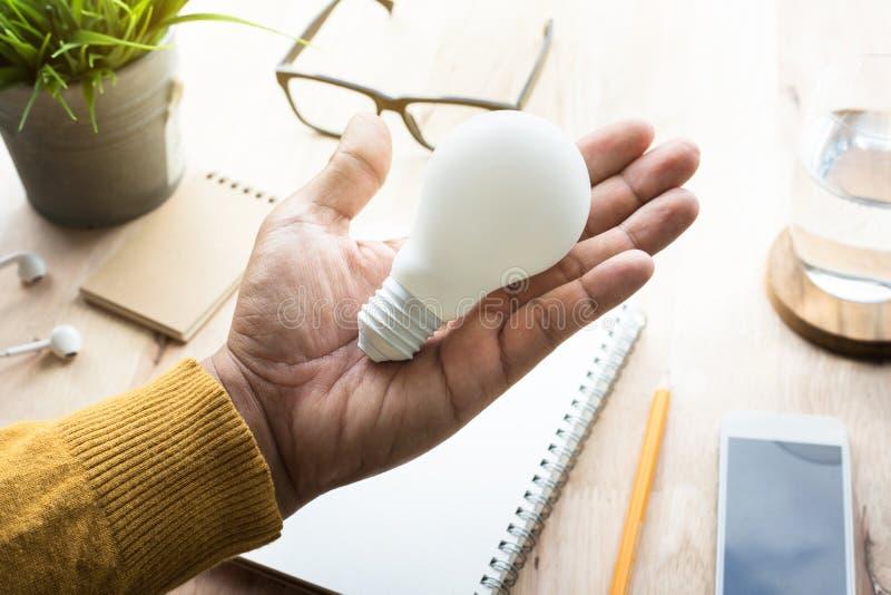 Uomo d'affari con la lampadina in posto di lavoro Idee, creatività fotografie stock