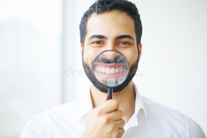 Uomo d'affari con la lente d'ingrandimento che zuma sul suo sorriso fotografia stock libera da diritti