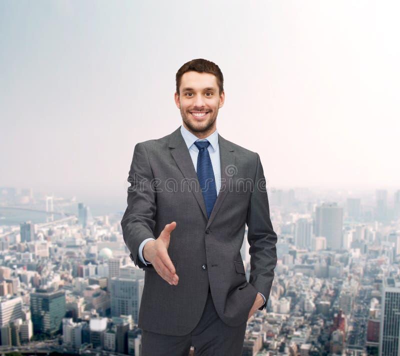 Uomo d'affari con la mano aperta pronta per la stretta di mano fotografia stock
