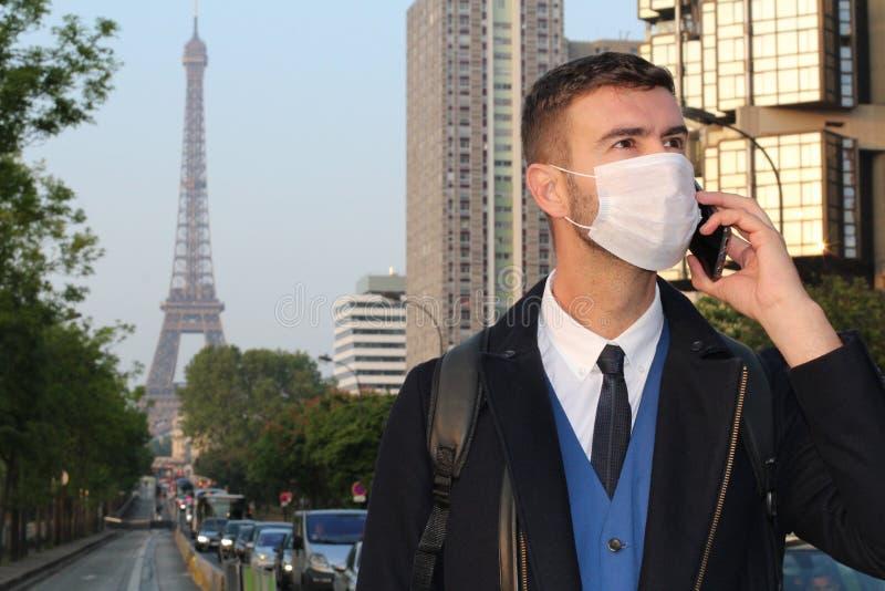 Uomo d'affari con la maschera di inquinamento che chiama dal telefono a Parigi fotografia stock libera da diritti