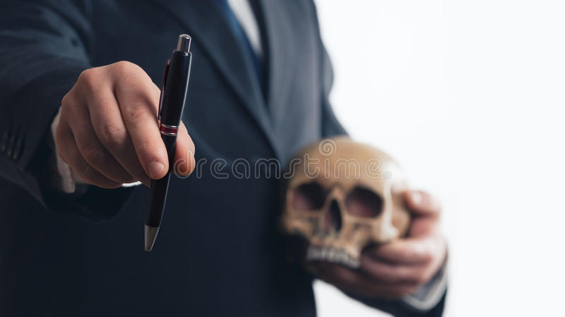 Uomo d'affari con la penna ed il cranio fotografia stock libera da diritti