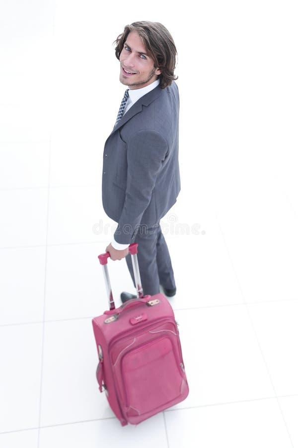 Uomo d'affari con la valigia di viaggio che esamina la macchina fotografica immagini stock libere da diritti