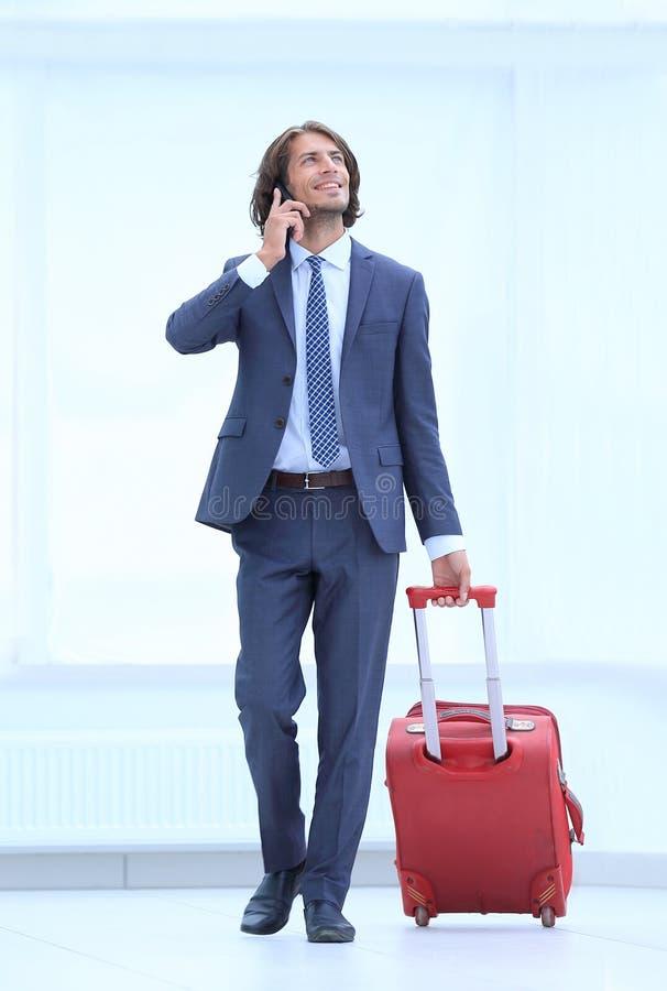 Uomo d'affari con la valigia di viaggio che parla sul telefono immagini stock libere da diritti
