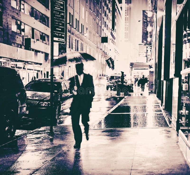 Uomo d'affari con la via bagnata della città dell'ombrello fotografia stock