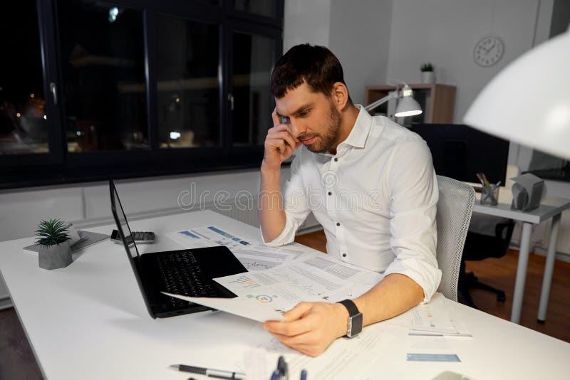 Uomo d'affari con le carte che lavorano all'ufficio di notte fotografia stock
