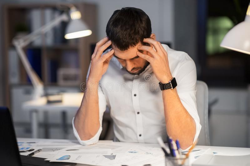 Uomo d'affari con le carte che lavorano all'ufficio di notte fotografie stock libere da diritti