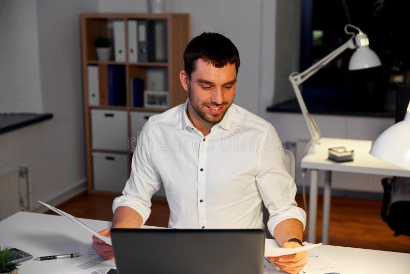 Uomo d'affari con le carte che lavorano all'ufficio di notte fotografia stock libera da diritti