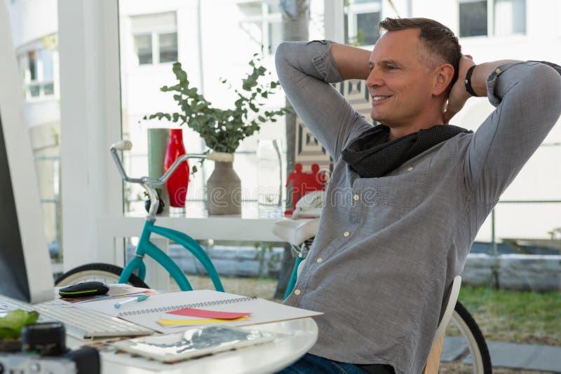 Uomo d'affari con le mani dietro la testa che si siede allo scrittorio in ufficio fotografia stock libera da diritti