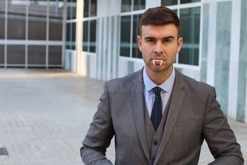 Uomo d'affari con le zanne del vampiro nell'ufficio fotografia stock libera da diritti